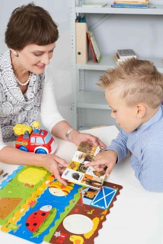 Logopedė Gražina Tumienė mokina vaiką logopedinio užsiėmimo metu. Rodomos kortelės ir lavinami vaiko motoriniai ir vizualiniai įgūdžiai.
